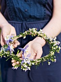 A girl holding a freshly made floral wreath