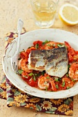 Fried sea bass on a bed of shrimps and tomatoes