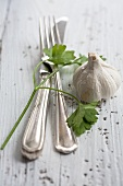Silver cutlery, flat-leaf parsley and a bulb of garlic