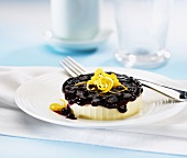 A small lemon cheesecake with blueberry sauce