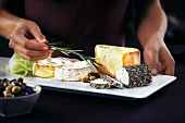 A cheese platter with olives and rosemary sprigs