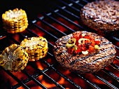 Hamburgers and sweetcorn on a barbecue