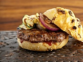 A gratinated hamburger with grilled vegetables and cheddar