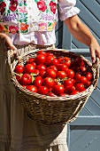 A woman in a traditional Hungarian blouse holding a basket of tomatoes