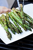 Removing Grilled Asparagus Spears from Grill and Placing on a Platter