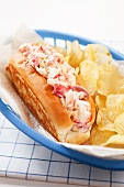 Lobster Roll with Potato Chips in a Plastic Take Out Basket