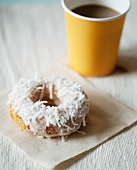 Coconut Doughnut on a Napkin with Coffee in a Paper Cup