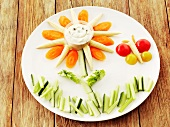 Teller mit lustiger Rohkost und Kräuterquark-Dip für Kinder (Rohkost: Gurken, Karotten, kleine Maiskolben, Tomaten)