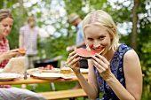 Lady eating watermelon at a barbeque