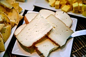 Assorted Cheeses on White Plates; Sliced and Cubed