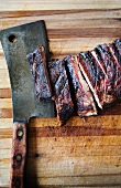 Barbecue Ribs on a Cutting Board with Rustic Knife