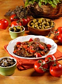 Bistecca alla siciliana (beef steak in tomato sauce with capers and olives, Italy)