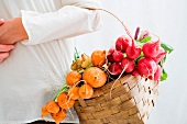 Woman holding basket of beetroot and radishes