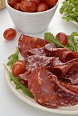 Two types of salami with cherry tomatoes on a plate