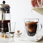 Pouring Cream into Glass Mug of Coffee
