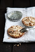 Mini Apple Pies with Crumb Topping on White Cloth; Mini Baking Tins in Background
