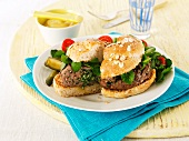 Hamburgers with lettuce, mustard and gherkins