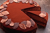 Chocolate torte, sliced, decorated with chocolate leaves