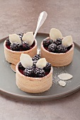Three small Baumkuchen (German layer cakes) filled with blackberry cream and garnished with blackberries, on a grey plate