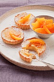 Three orange custard tarts and orange segments on a round tray