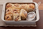 Cinnamon whirls with icing sugar in a baking tin