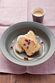 Two pieces of advocaat cake with pomegranate seeds in a light blue dish
