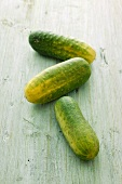 Three gherkins on a wooden surface