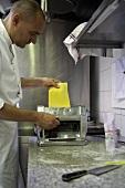 Koch lässt Nudelteig durch die Nudelmaschine