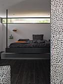 Designerbett mit Metallstange von der Decke abgehängt vor umlaufendem Fensterband, im Vordergrund mit Kieselmosaik geflieste Wand und dunkler Parkettboden