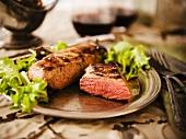 A Whole Tri-Tip Steak with Half a Tri-Tip Steak on a Plate