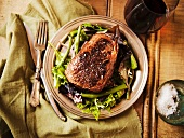 Grass Fed Sirloin Steak on a Bed of Greens; From Above; With Wine