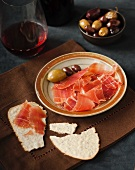Spanish Jamon Ibérico with crackers, olives and red wine