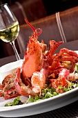 Whole Lobster with Fresh Greens on a Plate; Glass of Chardonnay