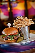 Beef Sirloin Burger with Smoked Bacon, Aged Goat Cheddar Cheese, Tomato Confit, Baby Arugula and Garlic Chive Aioli; Pickle and French Fries