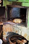 Alter Holzofen mit Brot auf Holzschaufel