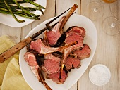 Carved Rack of Lamb on a Platter with a Platter of Asparagus; From Above
