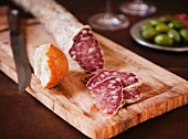 Salami Sliced on a Cutting Board with Bread; Bowl of Green Olives in the Background