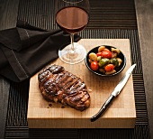 Whole Steak on a Cutting Board with a Bowl of Roasted Vegetables and a Glass of Red Wine