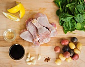 Raw Chicken Drumsticks with Ingredients; Soy Sauce, Garlic, Spinach, Potatoes and Lemon