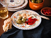 Plate with a Single Serving of Tapas; Green Olives, Roasted Red Peppers and Almonds; Bread and White Wine