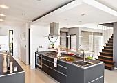 Freistehende Küchentheke mit grauen Oberflächen unter abgehängter Decke in modernem, offenem Wohnraum mit Treppenaufgang