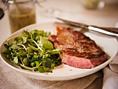 Center Cut Strip Steak with Mixed Greens on a Plate