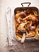 Roast chicken legs on a bed of oven-roasted vegetables in a roasting tin