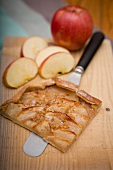 A slice of apple tart and fresh apples