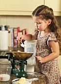 Kleines Mädchen beim Mehl abwiegen
