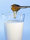 Honey dripping into a glass of milk