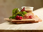 Salad ingredients: lettuce, Parma ham, raspberries and dressing