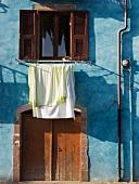 Pastellblaue Hausfassade eines sardischen Hauses mit trocknender Wäsche