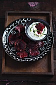 Beetroot chips with a quark dip on a black patterned plate