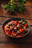 Chilli con carne in a black bowl on a wooden surface